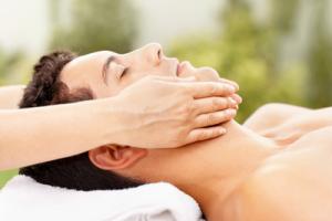 Twarz mężczyzny w dłoniach masażystki