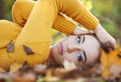 Kobieta leży na jesiennych liściach