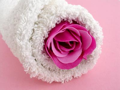różowy kwiat wyłaniający się z zrolowanego ręcznika
